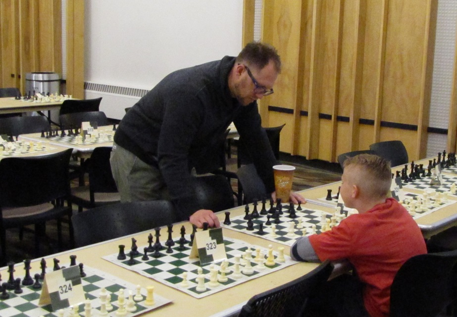 grownup plays chess with a kid